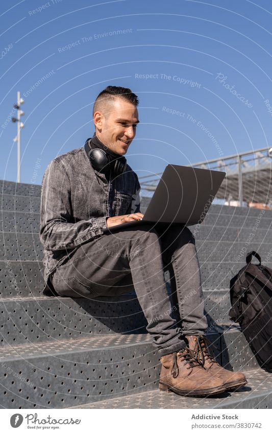 Cheerful young man working on laptop in headphones using typing cheerful internet freelance browsing stairs occupation male remote device modern surfing