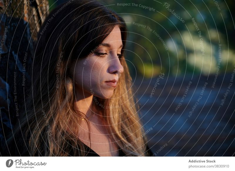 Serious pensive woman standing near tree sad silent thoughtful alone lonely serious upset melancholy think unhappy problem depression mood female young trunk