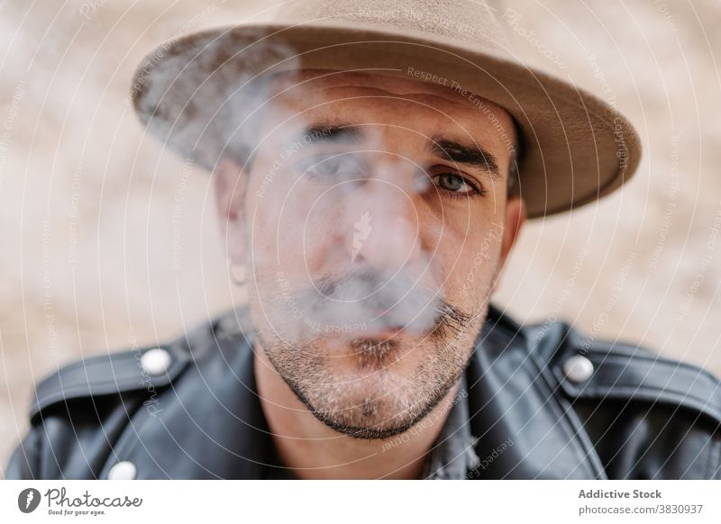 Serious pensive man in hat smoking cool smoke cigarette mustache hipster brutal rest contemplate male peaceful modern confident relax ponder concentrate