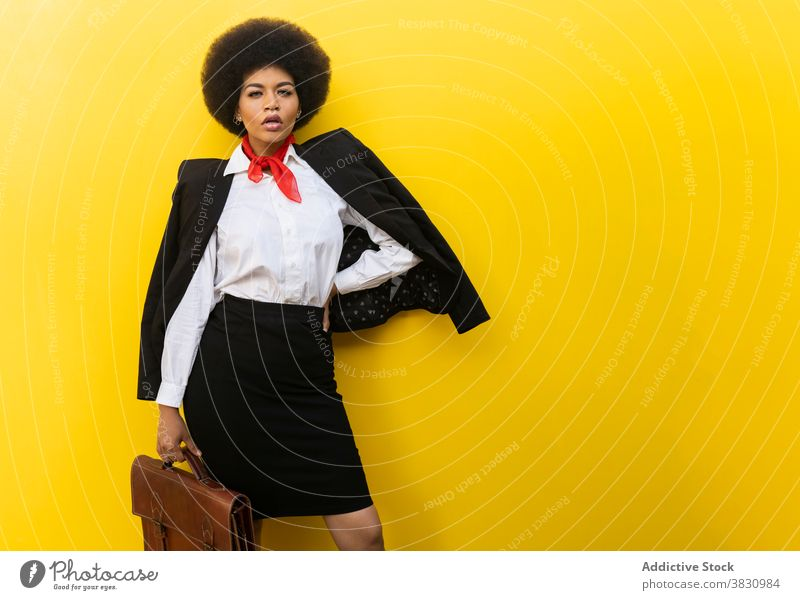 Stylish black woman in suit and blouse with briefcase style serious confident hand on waist executive respectable classy well dressed formal female studio shot