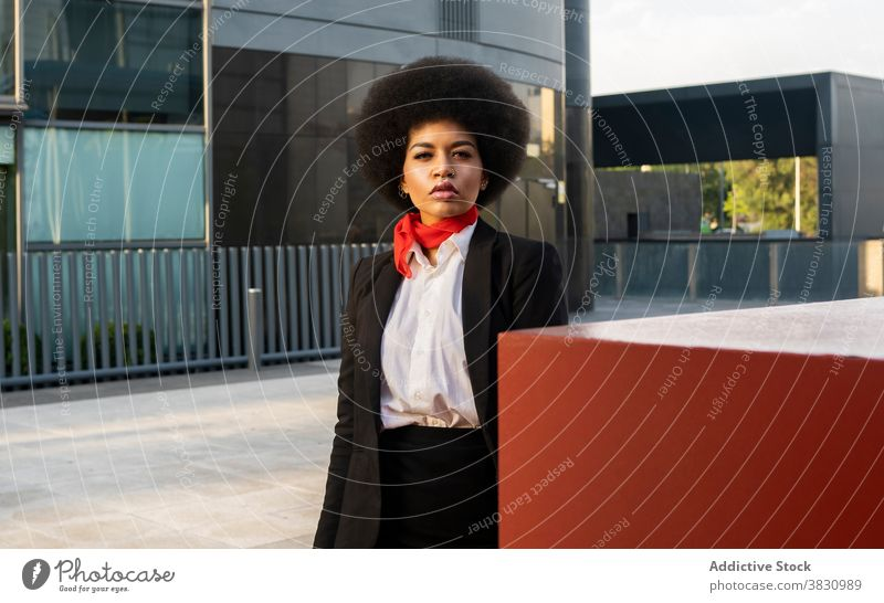 Confident black woman in formal outfit standing near colorful wall concentrate employee elegant occupation worker respectable style confident female serious