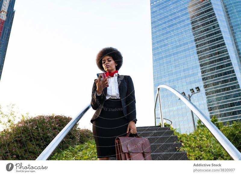 Black businesswoman on smartphone confident call using entrepreneur listen formal conversation executive female briefcase serious mobile device professional
