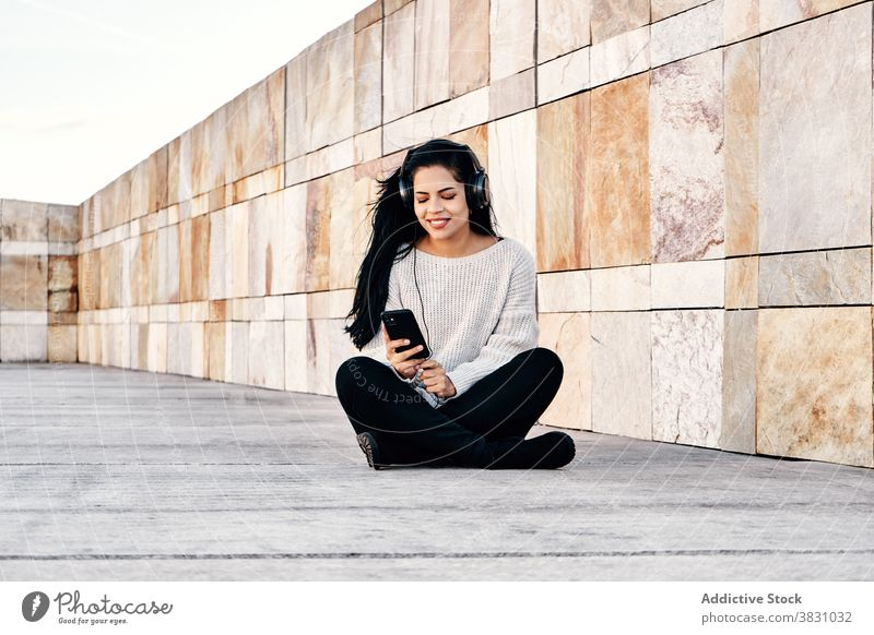 Delighted ethnic woman listening to music on street smile wall marble legs crossed headphones happy female audio melody optimist casual tune rest lifestyle