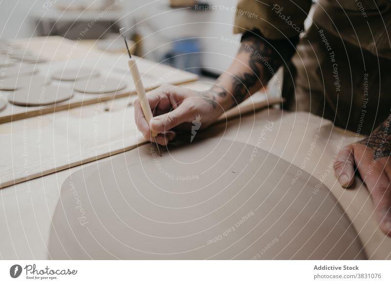 Crop ceramist creating handmade clayware in workshop create artisan pottery earthenware material tool sharp piece handicraft skill equipment professional