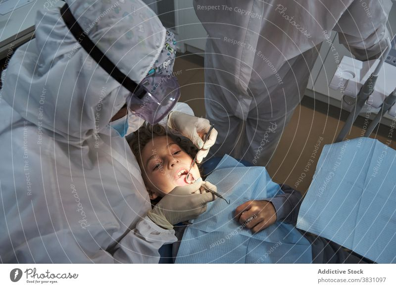 Dentist making oral treatment for kid in clinic dental dentist coronavirus child check teeth costume protect dentistry patient instrument lying chair glove