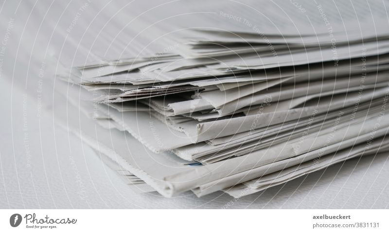 messy pile of newspapers or papers recycling print media heap stack information press journalism business publication current events concept recycle reading