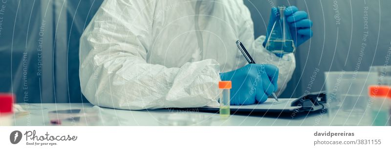Scientist with protection suit investigating in the laboratory scientist bacteriological protection suit test tube virus coronavirus taking notes vaccine