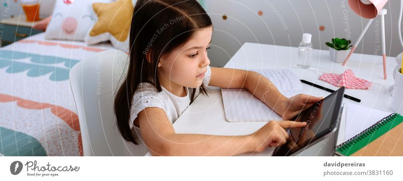 Girl studying at home with tablet and mask on table girl school at home home schooling coronavirus covid-19 digital wisdom social distancing banner header web