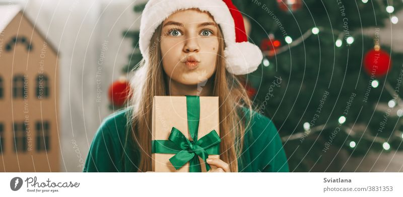 A beautiful girl with surprised eyes looks at the camera with a gift from kraft paper tied with a green ribbon. Christmas mood. Concept for New Years holiday at home.