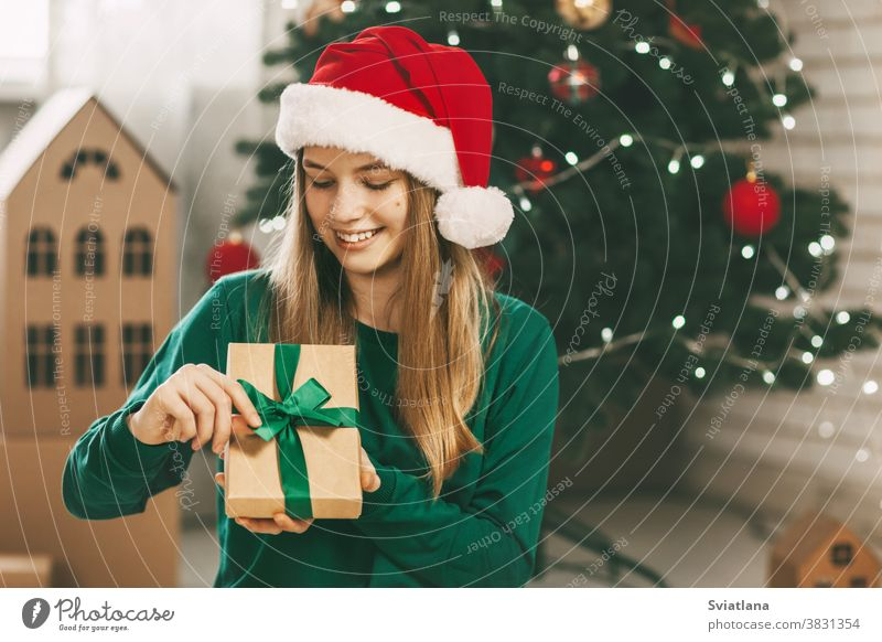 Beautiful teenage girl opens a gift made of kraft paper tied with a green ribbon, new year mood. Holiday concept of Christmas and New Year at home. christmas