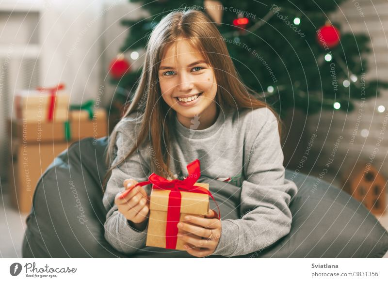 Beautiful teenage girl opens a gift made of kraft paper tied with a red ribbon, new year mood. Holiday concept of Christmas and New Year at home. christmas
