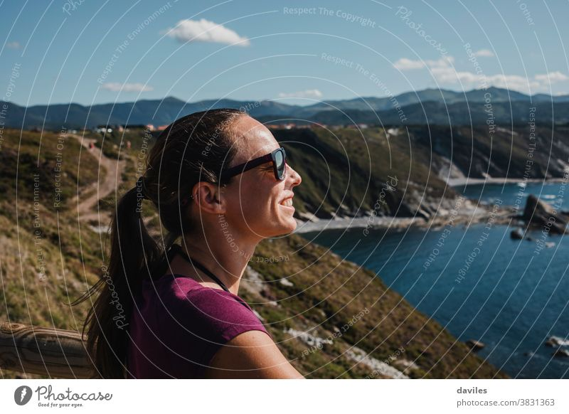White woman enjoying the sun and the views in the Cantabrian Sea, in Spain. north spain asturias relax casual t shirt adventure mountain top white nature teeth