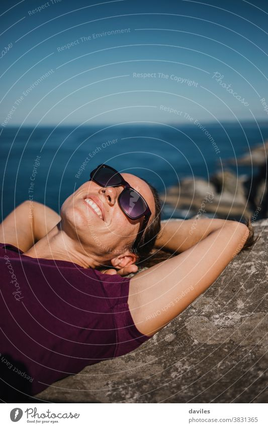 Lying woman on a rock, at the coast line with sunglasses and purple t shirt, and the sea in the background. smile waves water lying down arms ocean spain