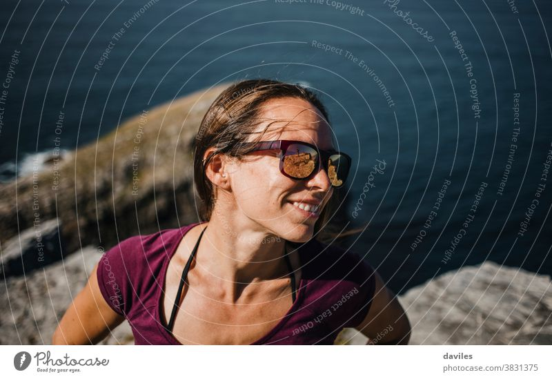 Happy natural woman portrait, with sunglasses, enjoying outdoors in the coast. exercise cheerful carefree happy relax standing waves sunny seashore coastline
