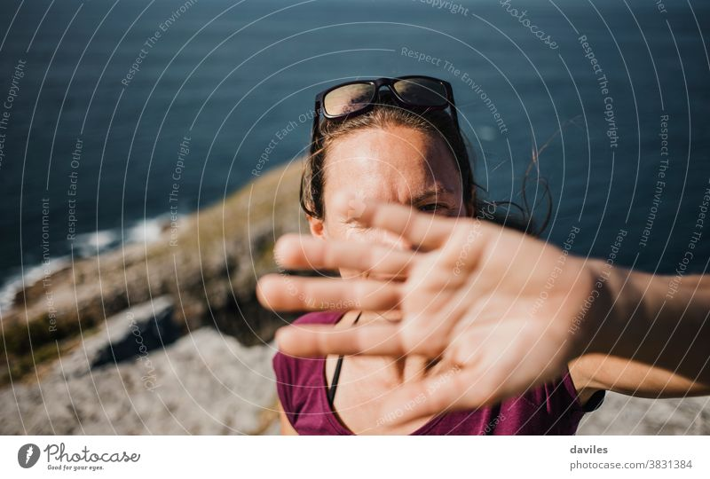 Playful woman trying to hide from photographer camera to avoid pics. mountain sea nature coast outdoors arm hand timid shame joyful playful shy expressive cover