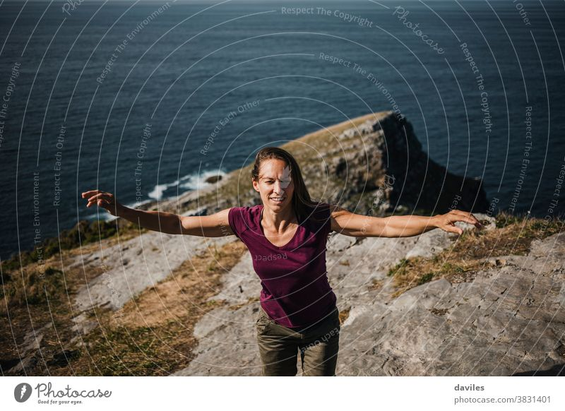 Woman raising arms while dance at the coastline on the top of a cliff, with sea in the background. nice inspirational sightseeing traveler elevation rock purple
