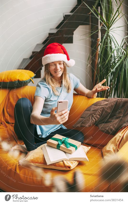 A smiling girl in a Christmas hat sits on the sofa and communicates via video link with friends. Girl congratulates friends and family on holidays christmas