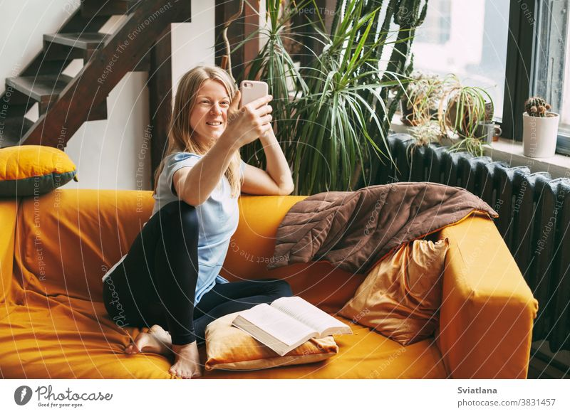 A young girl is sitting on the sofa and taking a selfie on her phone, an open book is lying next to her home woman cellphone room wireless text mobile internet
