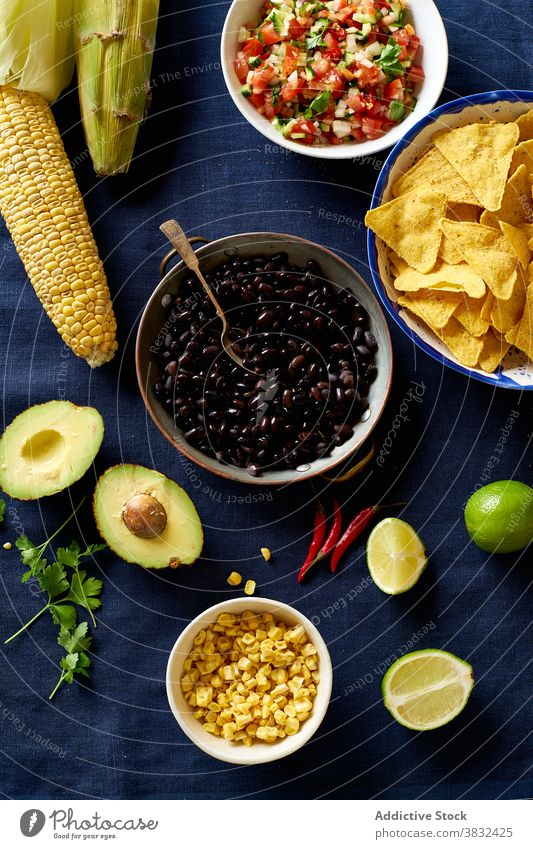 Ingredients for mexican cuisine food chilaquiles dish tortilla ear of corn breakfast black beans nachos cilantro sauce fried meal chips fresh salsa homemade