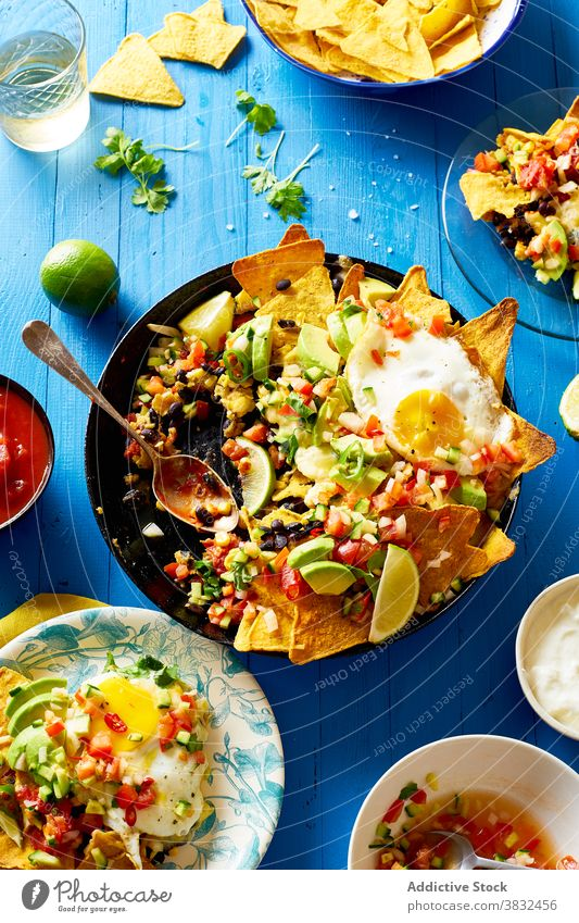 Chilaquiles dish with avocado food chilaquiles mexican tortilla top view breakfast overhead black beans nachos cilantro sauce fried meal chips fresh salsa