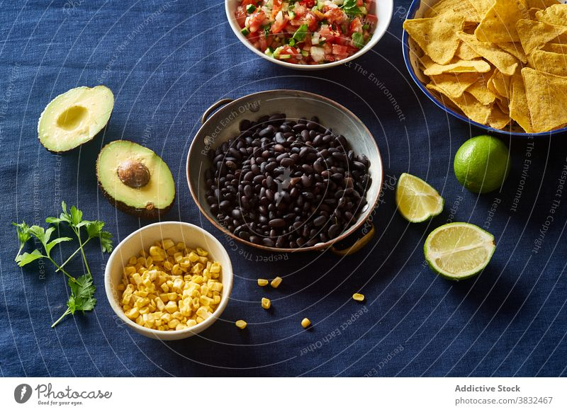 Ingredients for mexican cuisine food chilaquiles dish tortilla breakfast black beans nachos cilantro sauce fried meal chips fresh salsa homemade cheese onion