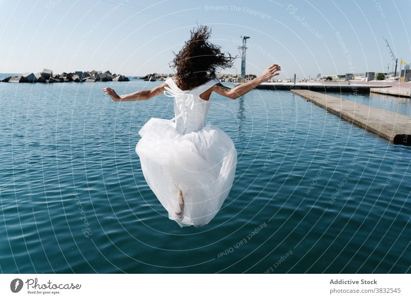 Anonymous woman in bridal dress falling in water white dress seafront lake pier young excited drown fun funky embankment afraid bodacious confused female lady