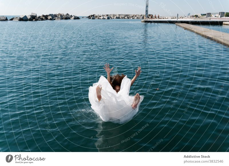 Anonymous woman in bridal dress falling in water white dress barefoot seafront lake pier young excited drown fun funky embankment afraid bodacious confused