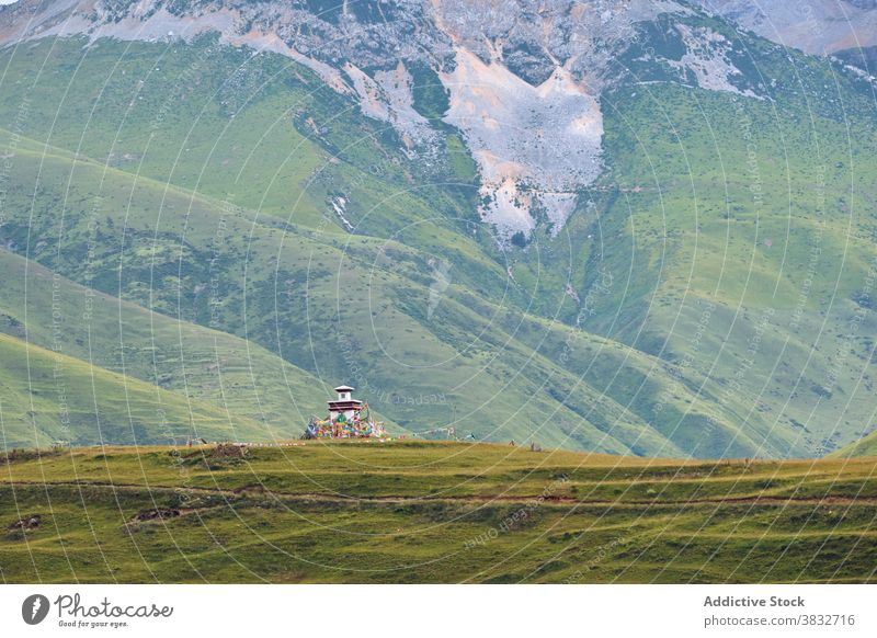 High mountains covered with greenery and shrine highland landscape slope valley building nature environment rock hill province rural house destination grass