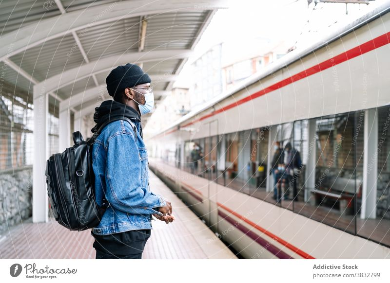 Black man on platform with train railway traveler mask coronavirus new normal tourist station male ethnic black african american backpack urban trip journey