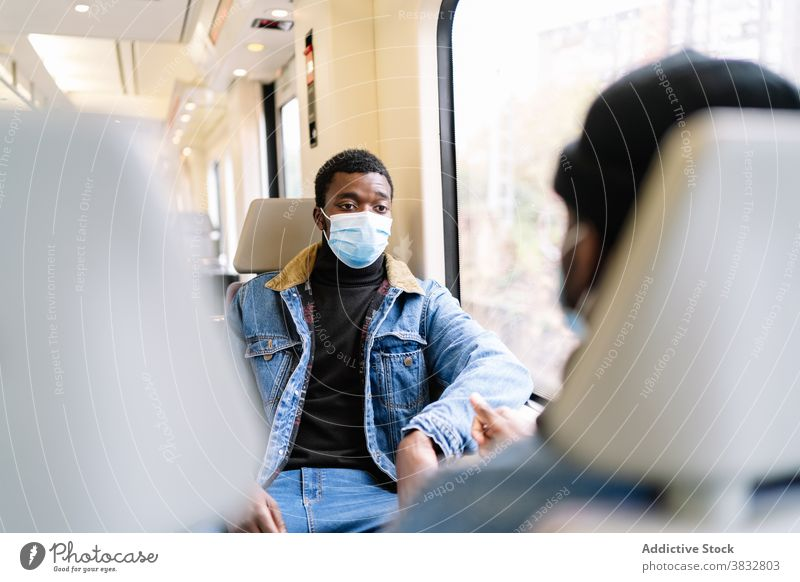 Male friends riding in train during coronavirus pandemic ride passenger men travel new normal window mask railroad ethnic black african american medical trip