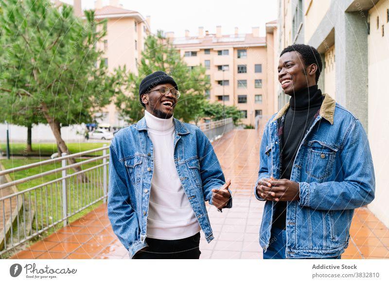 Delighted black men laughing in city having fun friend joke together style denim street ethnic african american happy cheerful friendship joy modern trendy
