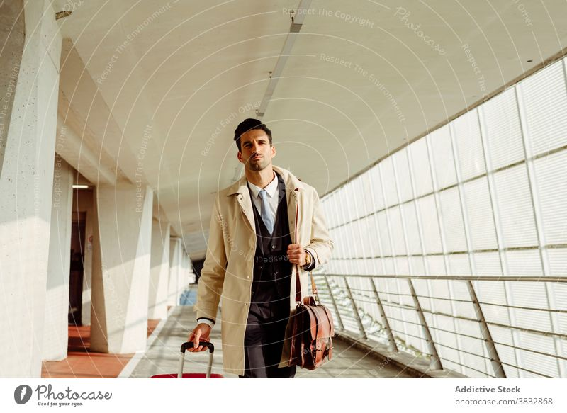 Stylish man walking along airport serious confident style suitcase pensive thoughtful corridor luggage male baggage ethnic modern departure passenger arrive