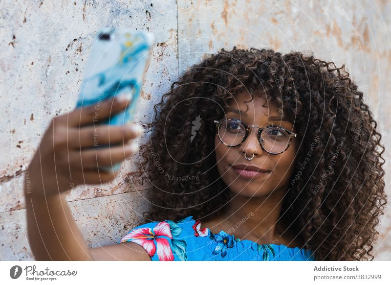 Glad black woman taking selfie near wall tree summer palm style smartphone weekend street rest female young ethnic african american glasses trunk casual trendy