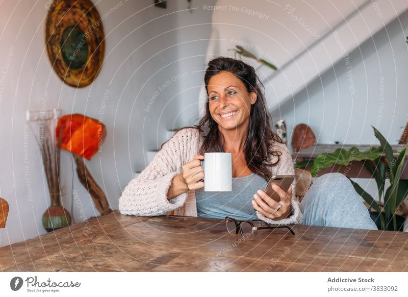 Happy woman with cup of coffee and smartphone sitting at table at home happy cheerful rest drink using adult ethnic female mobile device gadget beverage