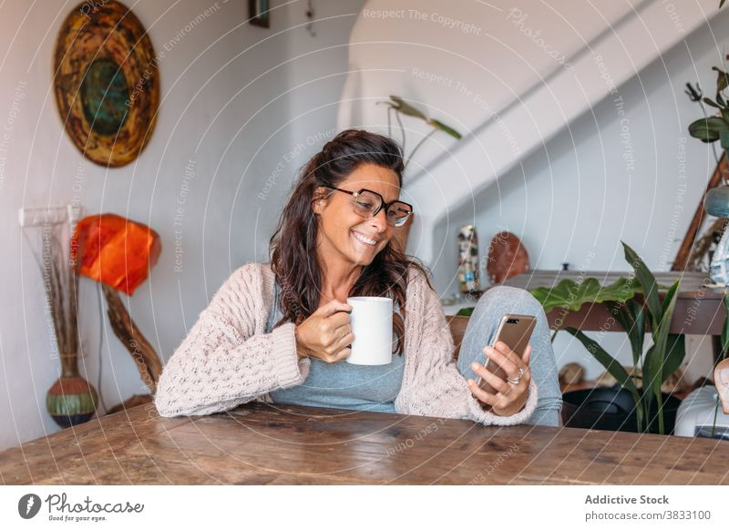 Positive ethnic woman with cup of coffee browsing smartphone at home happy cheerful rest drink using cozy comfort adult female mobile device gadget beverage