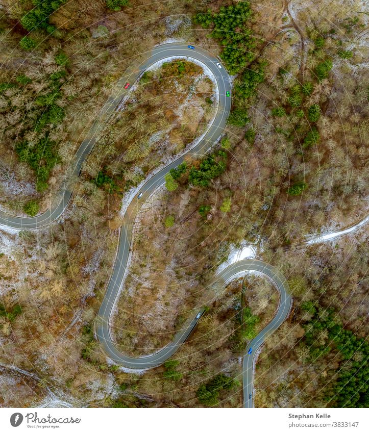 Winding road in the transition from autumn to winter, snow at a germany roa, filmed straight from above. background car tree nature eyecatcher ice view aerial