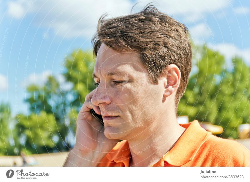 Man in orange clothes man male European Caucasian handsome talking phone mobile cellular white person brown shaten summer fall autumn outdoor casual thirty