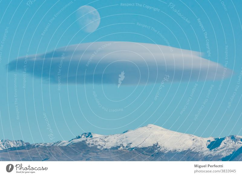 Landscape of Sierra Nevada in Granada with a lenticular cloud and the moon over it. Veleta peak mountain landscape tourism snow skiing Andalucia mountaineering