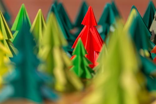 self made coloured fir trees made of paper stand in the forest Waldorf School Bazaar Red Green firs christmas trees Christmas tree Handicraft Self-made homemade