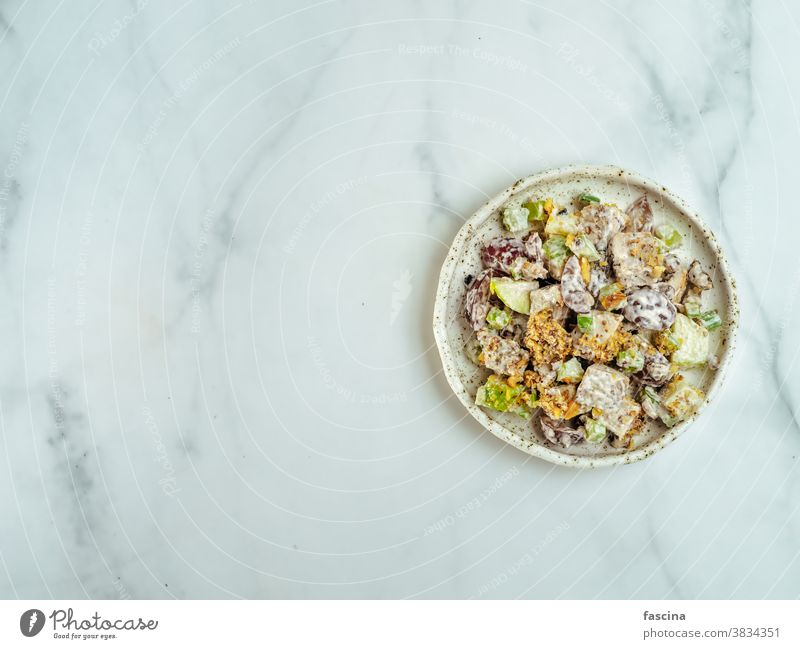 Waldorf salad on white marble,copy space,top view waldorf salad flat lay delicious tasty american fruit nut apples celery grapes chicken meat dressed vegetable
