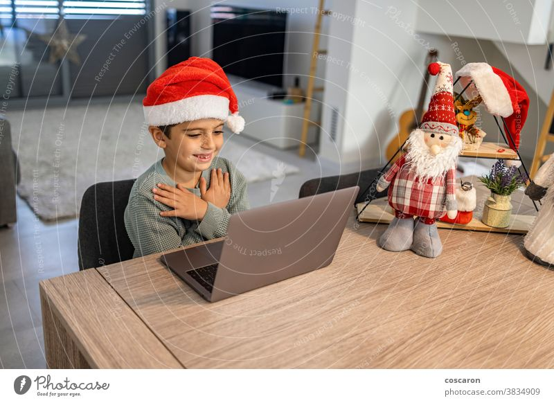 Little kid making a video call with the family on Christmas alone boy camera celebration chat child childhood children christmas claus communication computer