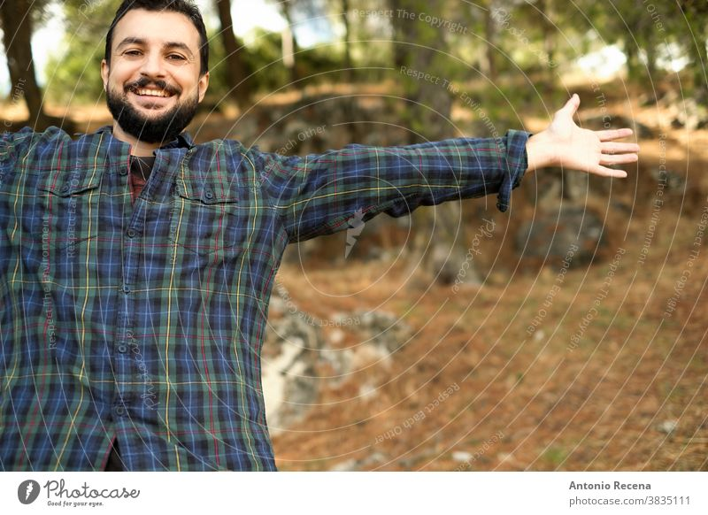 Man with beard and plaid shirt of aesthetic lumberjack spreads his arms in the middle of nature with joy man freedom forest woodcutter bearded emotion happy