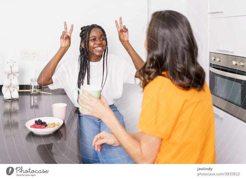 Two friends having a healthy snack while chatting at home women food eating multiethnic multiracial appetizer house vegetarian student black afro lifestyle girl