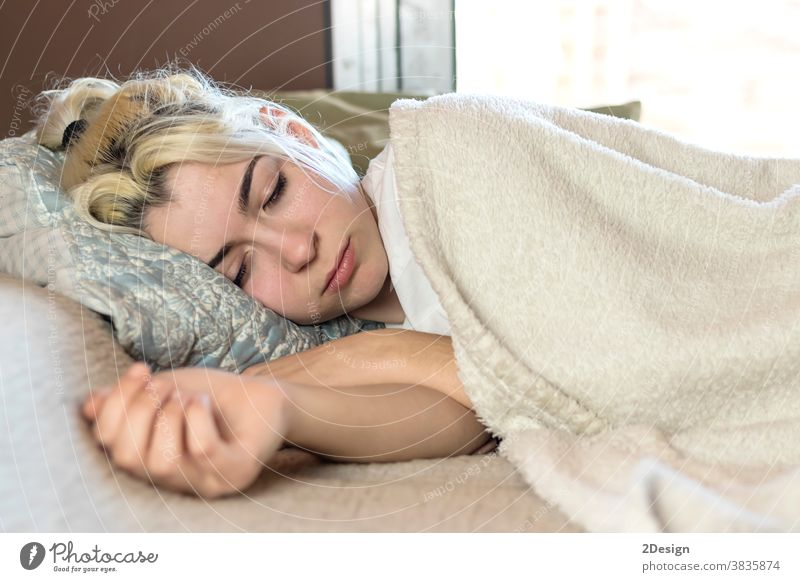 Beautiful young woman sleeping while lying in bed comfortably asleep dream dreaming human positivity awake bedding bedtime health informal pillow positive