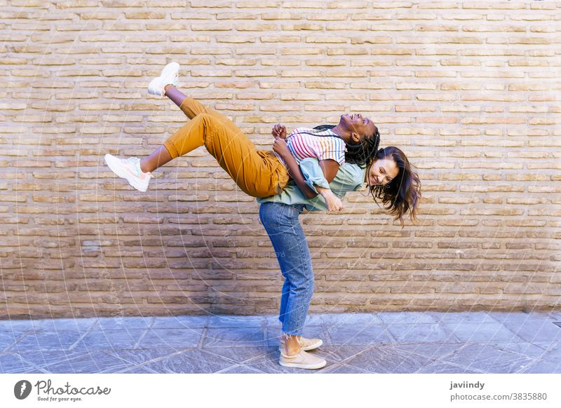 Funny multiethnic woman carrying her best friend piggyback fun black afro girl student two people lifestyle smile female young happiness friendship outdoors