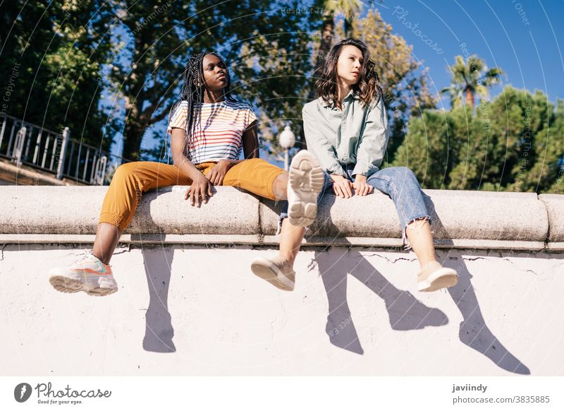 Two multiethnic women sitting on a urban wall. serious expression sunlight friend black afro girl student two people lifestyle female pretty young friendship