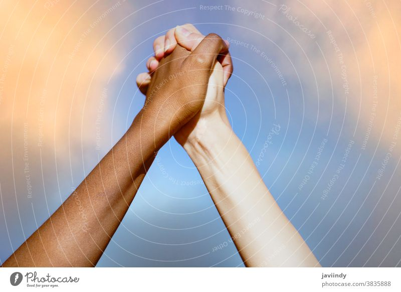 Multiethnic women's hands together against cloudy sky. multiethnic multiracial people black life matters african friendship caucasian blue diversity skin