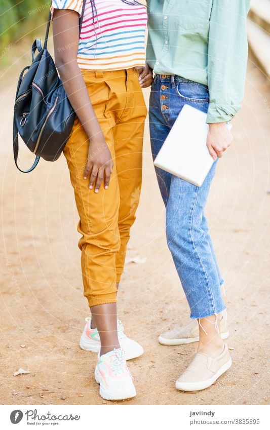 Two unrecognizable multiethnic girls posing together with colorful casual clothing woman friend tablet digital female young lifestyle urban beautiful device