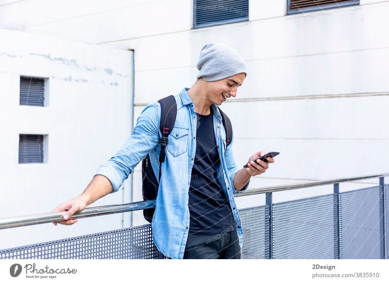 Urban stylish young man standing by the wall using cellphone smartphone talking calling guy mobile male technology city lifestyle urban communication