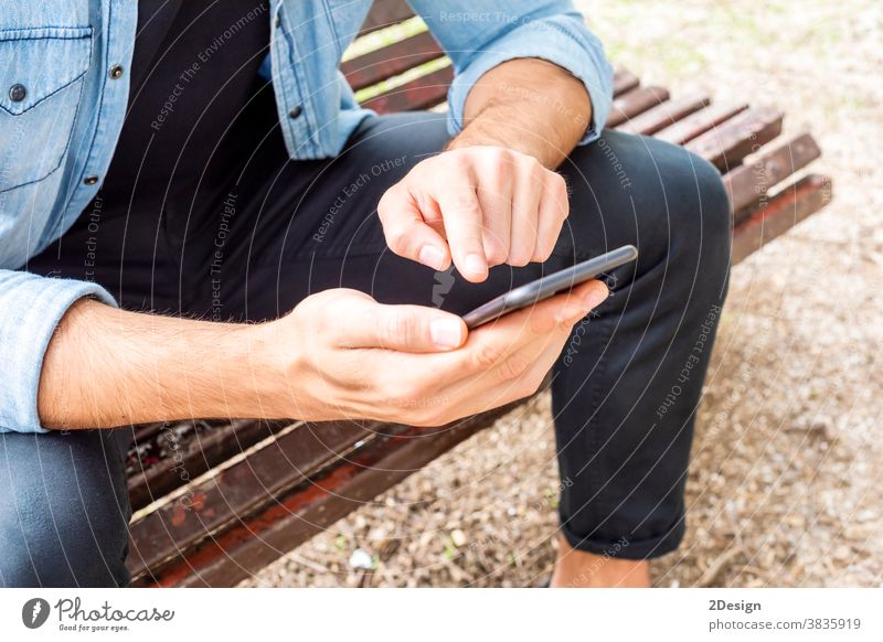 Closeup up an Attractive young man sitting on a bench outside using his cell phone outdoors holding mobile phone smiling urban male person lifestyle city